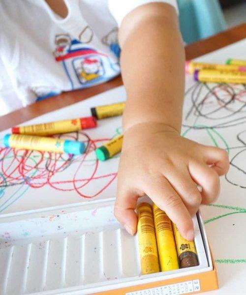 bambina prende un pennarello giallo per colorare un disegno