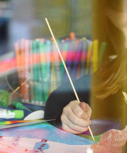 bambina colora un disegno al baby club