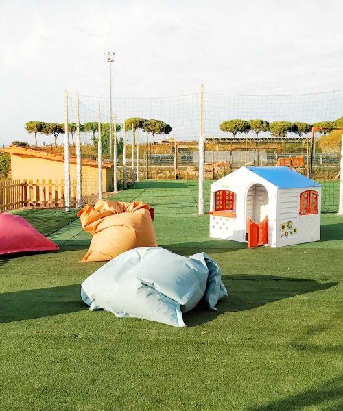 casetta per bambini colorata e cuscini colorati sparsi sul prato